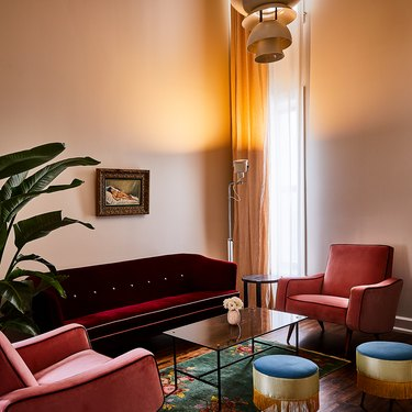 art deco living room with red velvet sofa, pink velvet armchairs, sleek coffee table and fringed footstools