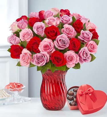 pink and red roses in red vase and box of chocolates