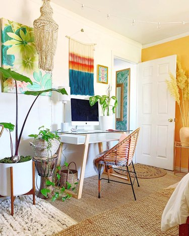 a colorful boho office with a yellow accent wall