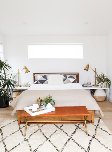 midcentury modern style bedroom with white walls and leather accent bench and area rug
