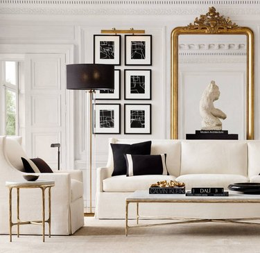 white art deco living room with large, ornate floor mirror and white sofa