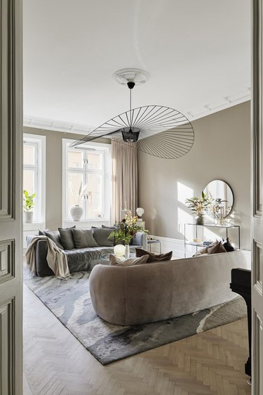 Gray and beige art deco living room with dramatic, black fan frame pendant light and cream colored sofas