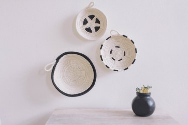 Three DIY cotton rope bowls hung on wall black and white graphic patterns