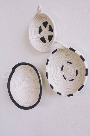 Three DIY cotton rope bowls hung on wall painted in black and white patterns