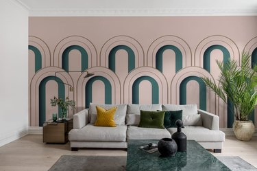 art deco living room with green arches on pink wall behind sofa