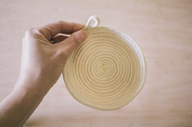 Tail of rope rolled into a loop shape and glued in place on the rim of the bowl