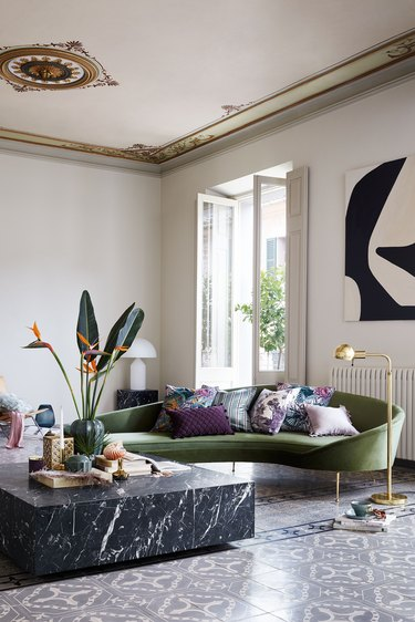 gray and white art deco living room with curved, green velvet sofa and large black marble coffee table