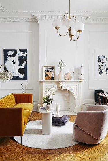 white art deco living room with orange sofa and wall art