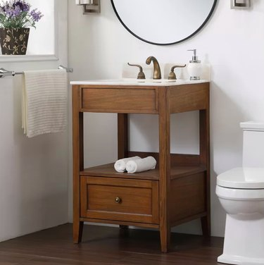 wood bathroom vanity with white toilet nearby
