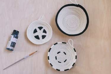 Three cotton rope bowls painted with black graphic patterns