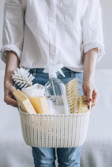 Woman holding cleaning supplies in basket