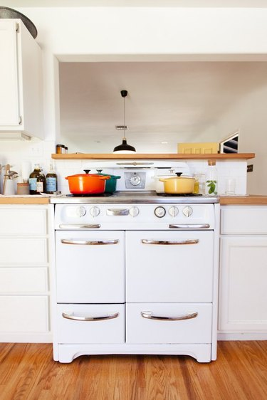 White oven with colorful pots on the stovetop