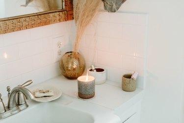 White subway tile bathroom backsplash idea with candle and bohemian decor details