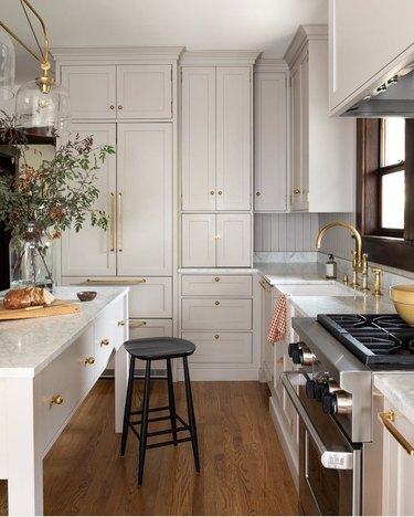 White craftsman kitchen cabinets with brass pulls and hardwood floor