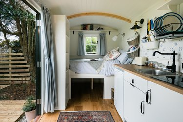 indoor-outdoor tiny house with bed and kitchen