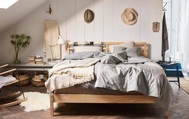 bedroom space with wood frame and two hats hanging on the wall