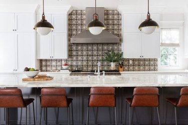 long wooden gray kitchen island with leather bar chairs and intricate tile backsplash