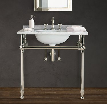 console style open vanity with marble countertop and polished chrome fixtures