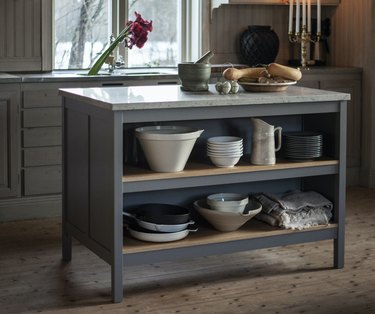 small wooden gray kitchen island with marble top and storage