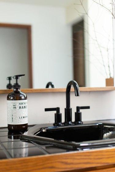 black tiled countertop with black drop in bathroom sink