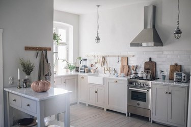 small gray kitchen island made of wood with two drawers in area with exposed range hood