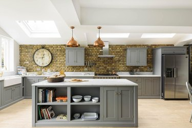wooden gray kitchen island with open and closed storage and copper ceiling lights