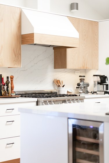 view of kitchen with light stone backsplash, cooktop and venting