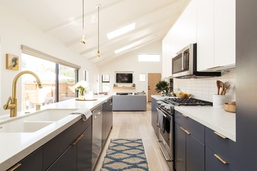 galley kitchen with blue lower cabinets and white countertops