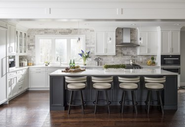 classic gray kitchen island with wood detailing on a glossy wooden floor