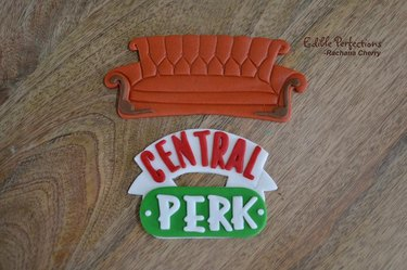 two cake topper in the shape of a couch and Central Perk logo