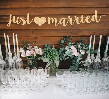 just married banner above glassware, candles, flowers