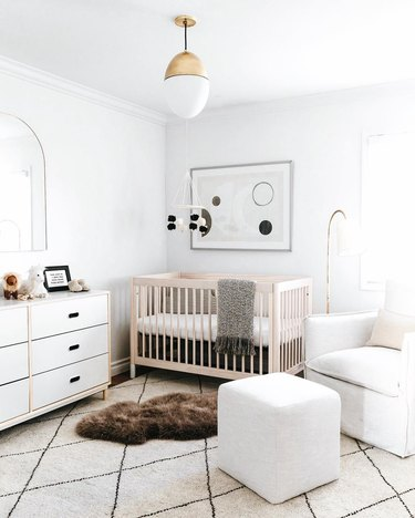 All-white gender neutral nursery with white armchair, white dresser, blonde wood crib, and geometric black and white print and felt mobile.