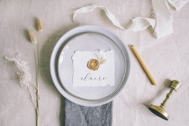DIY gold wax seal place card with dried florals on top of place setting on table