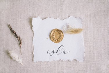 Gold wax seal and dried flowers glued to center of raw edged place card