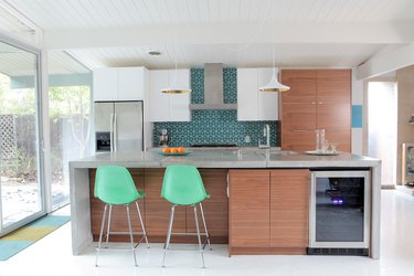 Midcentury-inspired kitchen with DIY waterfall concrete island and wood cabinets