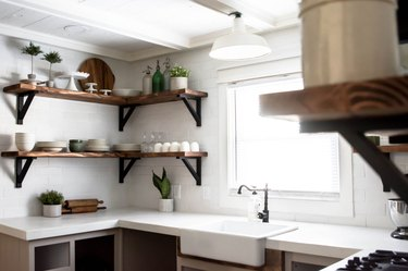 Kitchen with white concrete countertop and open wood shelving