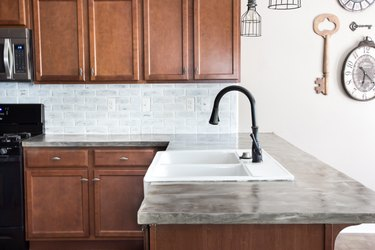 Feather-finish concrete kitchen countertops in with wood cabinets and white-washed brick backsplash