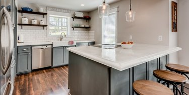 Modern kitchen with open wood shelving, gray cabinets, island and white concrete countertops.