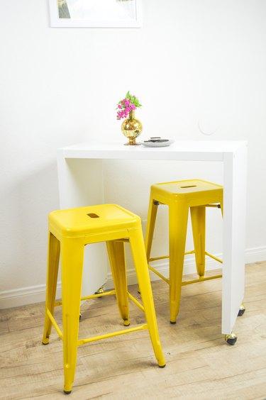 IKEA kitchen island with yellow bar stools in white kitchen