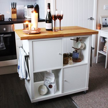 IKEA kitchen island with wood countertop and white cabinets