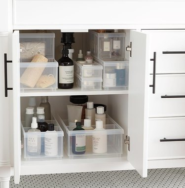 Multi size and shape plastic storage containers inside a cabinet underneath a bathroom sink