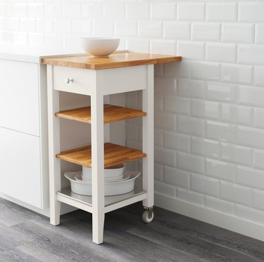 Small IKEA kitchen island with oak and white details against white subway tile backdrop