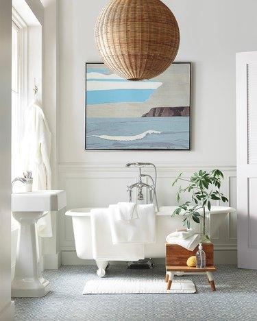 Rattan round coastal bathroom lighting idea in white bathroom alongside freestanding bathtub and coastal artwork