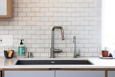 close up of kitchen sink with subway tile backsplash