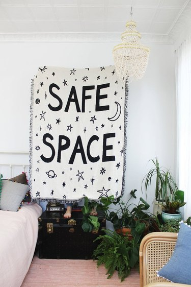 """living room space with large black and white blanket with the words """"safe space"""""""