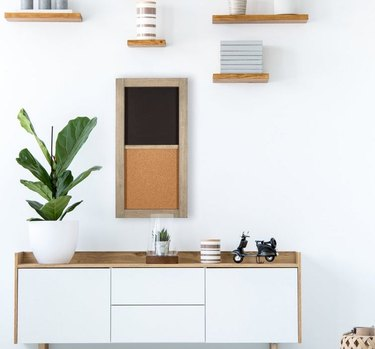 home space with credeza and chalkboard and corkboard combination on the wall, hanging floating shelves above