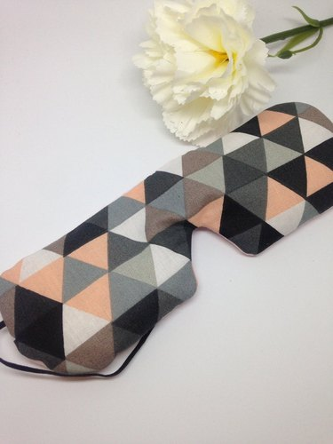 geometric patterned eye mask with flower nearby