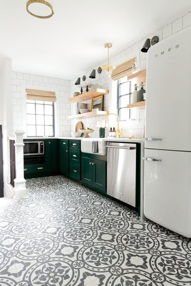 Black and white patterned tile modern kitchen flooring in modern kitchen with green cabinets