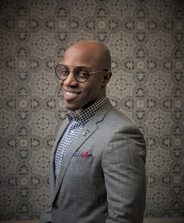 photo of designer corey damen jenkins standing in front of patterned wall