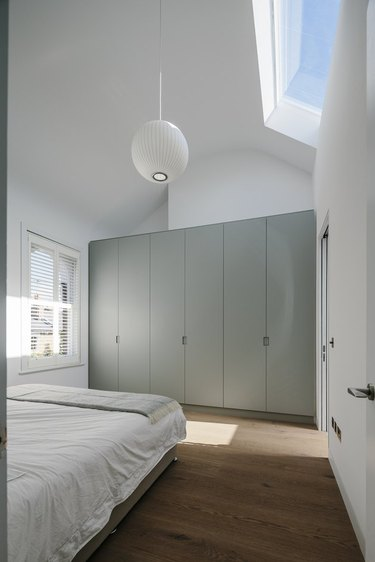 light, bright master bedroom with built-in closet and George Nelson pendant light